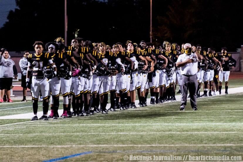 Varsity football players and coach stand together as they honor the flag.